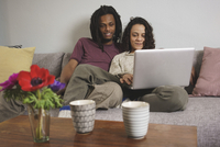 Young multi-ethnic couple using laptop while sitting on sofa at home