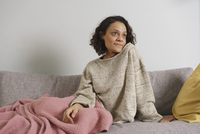 Thoughtful woman looking away while sitting on sofa at home 11016035597| 写真素材・ストックフォト・画像・イラスト素材|アマナイメージズ