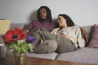 Cheerful multi-ethnic couple relaxing on sofa at home 11016035604| 写真素材・ストックフォト・画像・イラスト素材|アマナイメージズ