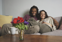 Portrait of happy multi-ethnic couple relaxing on sofa at home