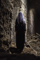 Full length of woman with obscured face standing in cave