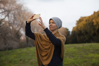 Mid adult woman photographing through smart phone on field against sky