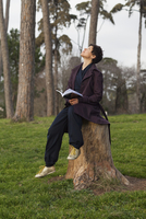 Full length of woman looking up while sitting on tree stump at field
