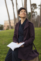 Thoughtful woman looking up while sitting on tree stump at field