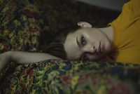 Portrait of beautiful young woman lying on bed