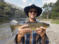 Portrait of happy mature man holding fish by river, Jindabyne, New South Wales, Australia