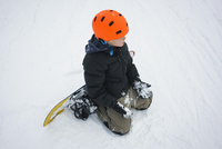 High angle view of boy with snowboard kneeling in snow