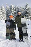 Full length portrait of brothers with snowboards standing on snow against trees