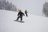 Boys snowboarding on slopes 11016035734| 写真素材・ストックフォト・画像・イラスト素材|アマナイメージズ