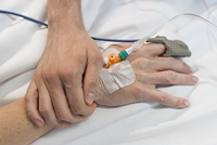 Close-up of man holding hand of a woman with IV drip at hospital