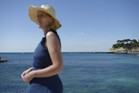 Side view of woman standing by seascape against clear sky