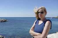 Woman with arms by sea against clear sky