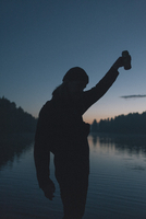 Silhouette of woman holding drink can by lake during sunset 11016035941| 写真素材・ストックフォト・画像・イラスト素材|アマナイメージズ