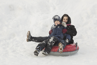 Portrait of happy grandmother and grandson sitting on inflatable ring in snow