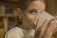 Close-up portrait of cute girl drinking milk at home