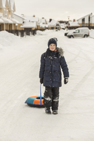 Full length portrait of boy pulling inflatable ring in snow