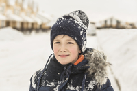 Portrait of confident boy in winter wear covered with snow