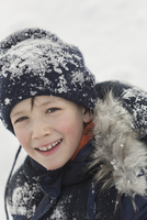Portrait of happy boy in winter wear covered with snow