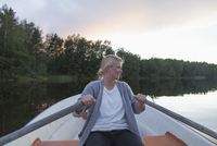 Happy woman rowing boat on lake against sky