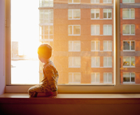 Side view of boy looking out while kneeling on window sill at home