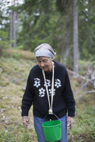 Senior woman carrying bucket in neck while walking on hill