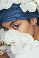 Portrait of woman hiding behind fresh white orchids