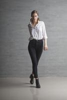 Portrait of confident beautiful fashion model walking against wall 11016036108| 写真素材・ストックフォト・画像・イラスト素材|アマナイメージズ
