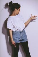 Beautiful fashion model making dog shadow on white wall 11016036124| 写真素材・ストックフォト・画像・イラスト素材|アマナイメージズ