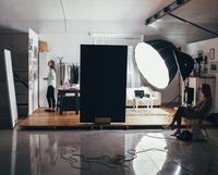 Female fashion designer and trainee with illuminated strobe lights at clothing studio 11016036149| 写真素材・ストックフォト・画像・イラスト素材|アマナイメージズ