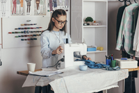 Female fashion designer using sewing machine at design studio 11016036158| 写真素材・ストックフォト・画像・イラスト素材|アマナイメージズ