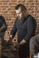 Male hairdresser mixing coffee while standing amidst coworkers against brick wall at barber shop