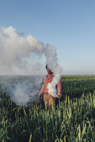 Man standing with distress flare emitting smoke on field against blue sky