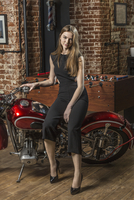 Portrait of beautiful smiling woman sitting on motorcycle by foosball table 11016036196  写真素材・ストックフォト・画像・イラスト素材 アマナイメージズ