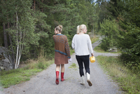 Rear view of women looking away while walking on dirt road amidst trees