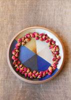 ブルーの柄の皿に並べたピンクのバラのドライフラワー