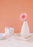 白い食器に飾ったピンクのガーベラの花と白いスプーン
