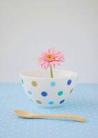 水玉の白い食器に飾ったピンクのガーベラの花と木のスプーン