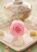 白い和食器の上のピンクのバラとストーン
