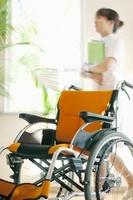 車椅子の後ろを歩く看護師