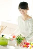キッチンにハーブを飾る女性