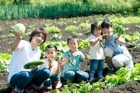 野菜を持ち微笑む家族