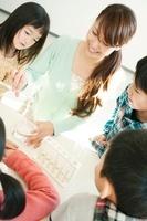 実験の授業をする先生と小学生
