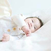 布団の上で微笑む赤ちゃん