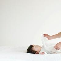 赤ちゃんに毛布をかける母親の手元