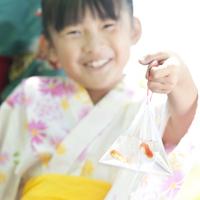 金魚の入った袋を持ち微笑む女の子