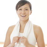 タオルを首に掛け微笑む女性