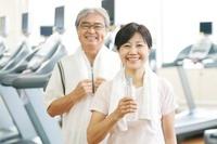 スポーツジムで水を持ち微笑むシニア夫婦