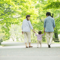 新緑の中を散歩する家族の後姿
