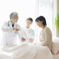 患者に病状の説明をする医者と看護師(訪問医療)