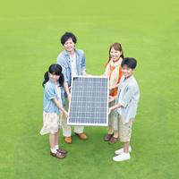 ソーラーパネルを持ち微笑む家族